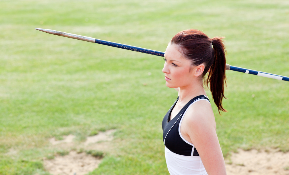 Concentrated female athlete ready to throw javelin in a stadium