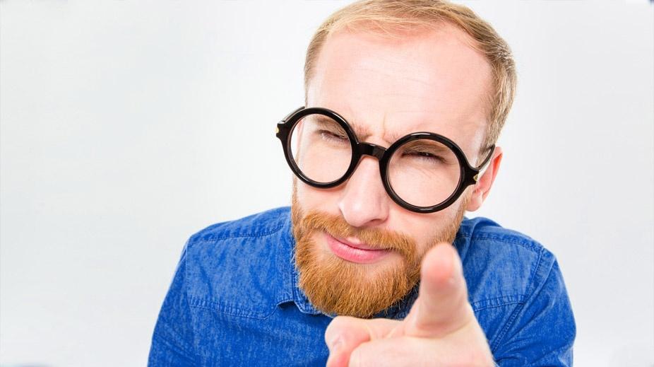 Portrait of suspicious young bearded man in funny round glasses pointing on you isolated over white background.jpeg